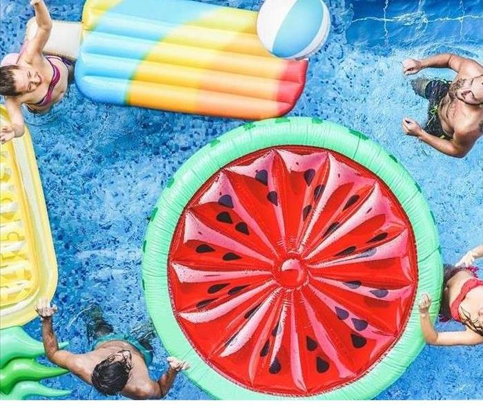 People are shown in a pool with floats
