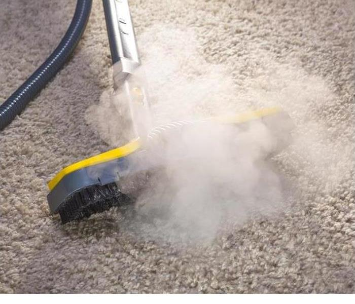 A steam cleaning device is shown on wet carpet