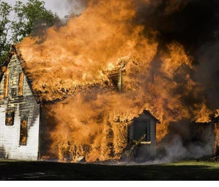 A home is shown to be completely surrounded by flames